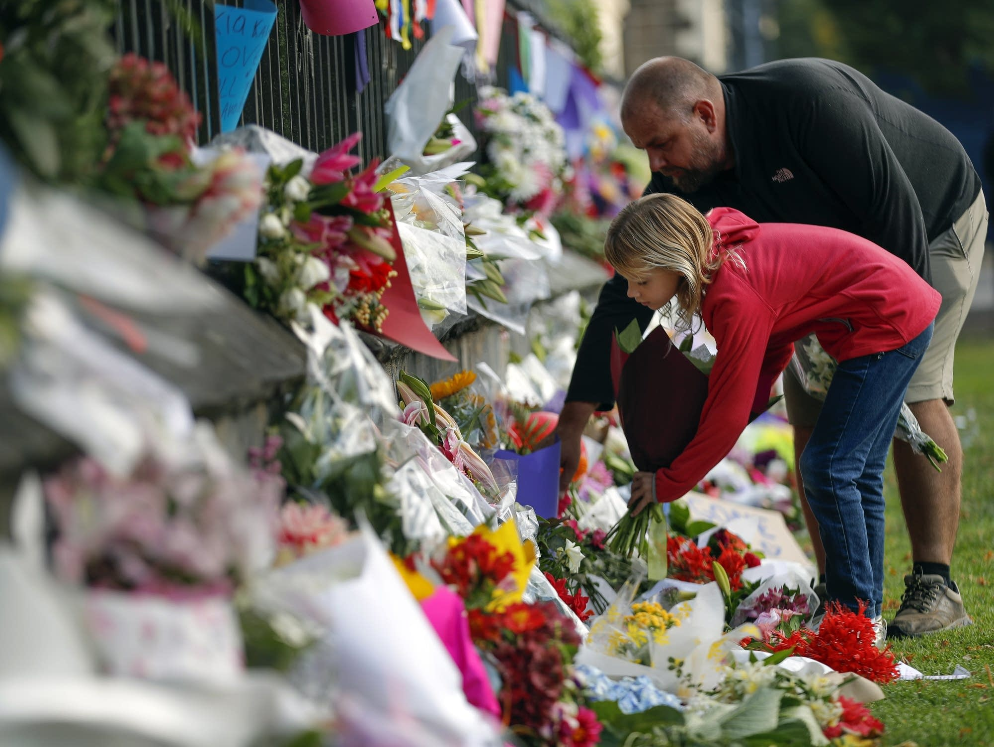 Mourners lay flowers on a wall in Christchurch, New Zealand
