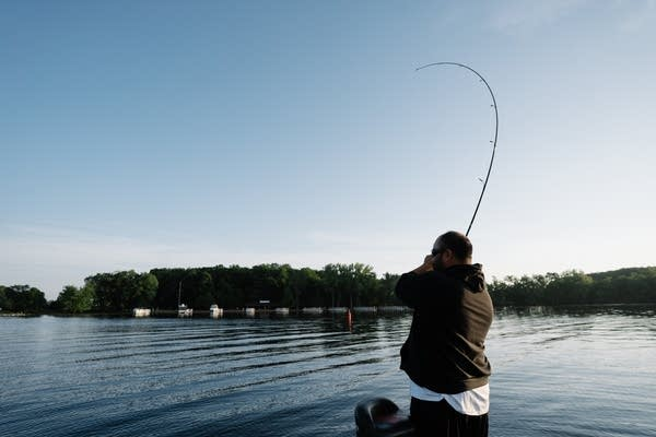 Daniel Heu sets the hook in a fish before reeling it in.