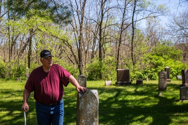 A man rests a hand on a headstone.