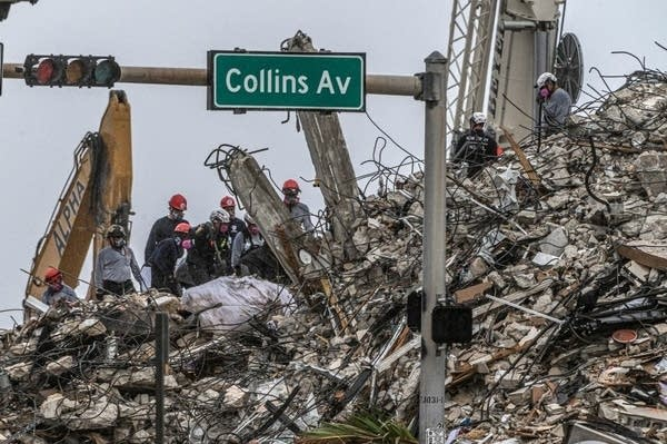 Rescue workers work at the site of a collapsed building.