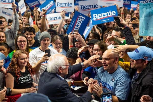 People reach out to shake hands with Sanders.