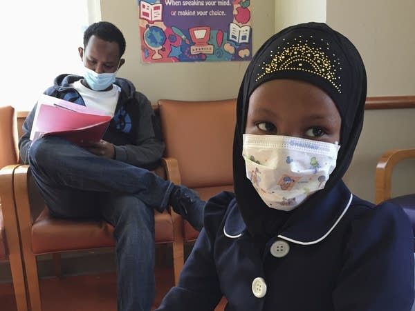Amira Hassan wears a mask to protect her as she plays in the waiting room.