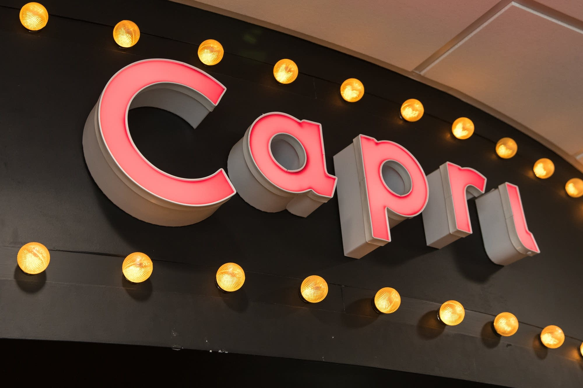 A fluorescent marque adorns the entrance of the Capri Theater.