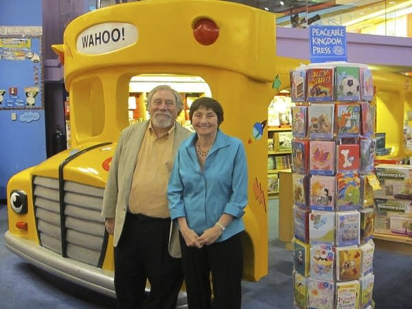 A man and a woman stand in a store with a large school bus display.