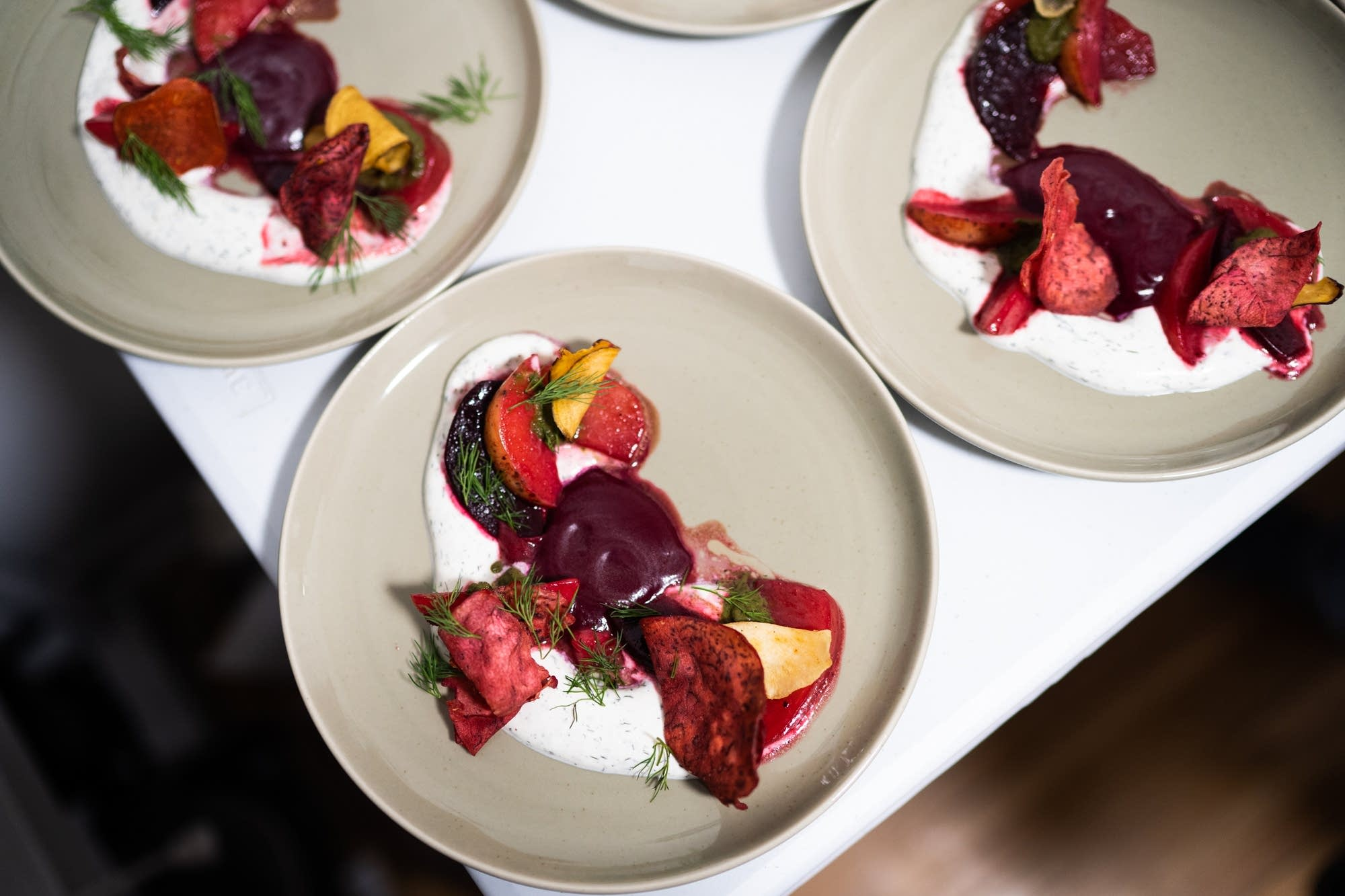 Roasted and fried root vegetables, dill sour cream, beet green puree.