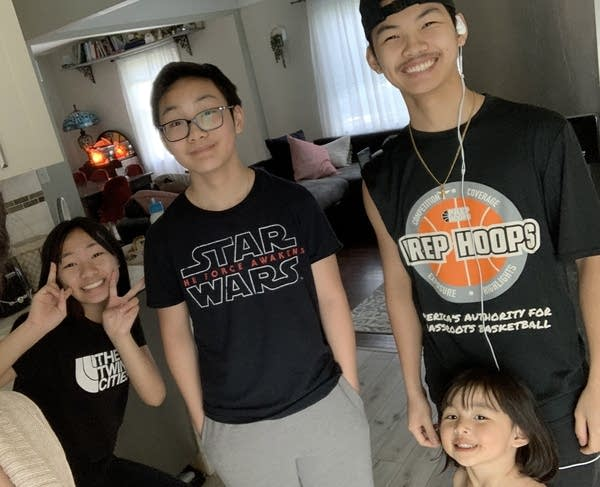 Four siblings stand in a room.