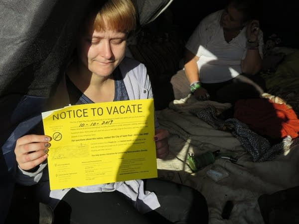 A woman holds a notice letter from the city of St. Paul.
