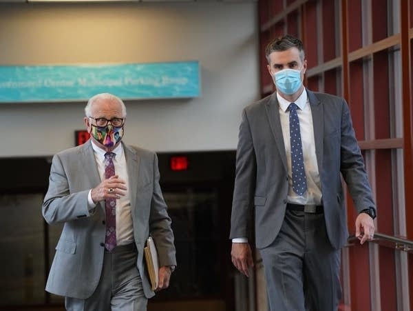 Men in suits with facemasks arrive at the courthouse