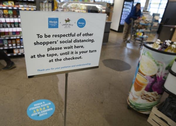 A sign marks the spot where people should wait at the checkout line.