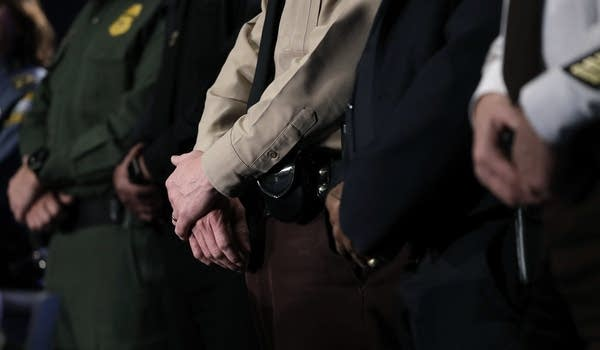 Law enforcement officers stand on stage during a security news conference.