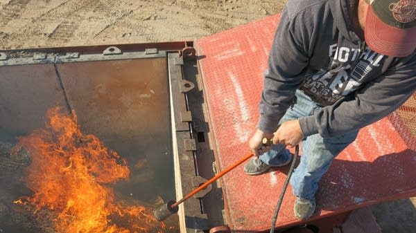 A man uses a blow torch to light the fire.
