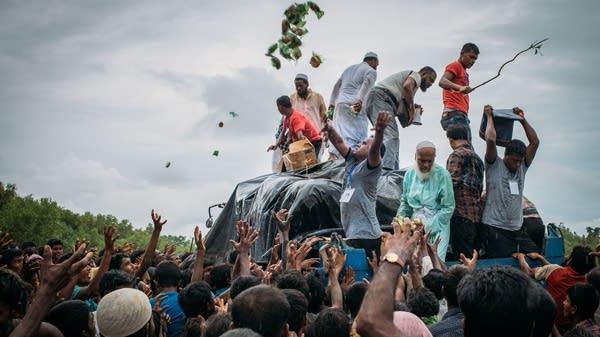 Bangladeshi volunteers distribute food to Rohingya Muslim refugees