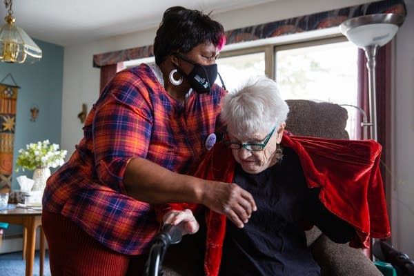 A woman helps another put on a coat.