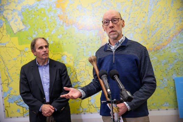 Two men speak in front of a map.