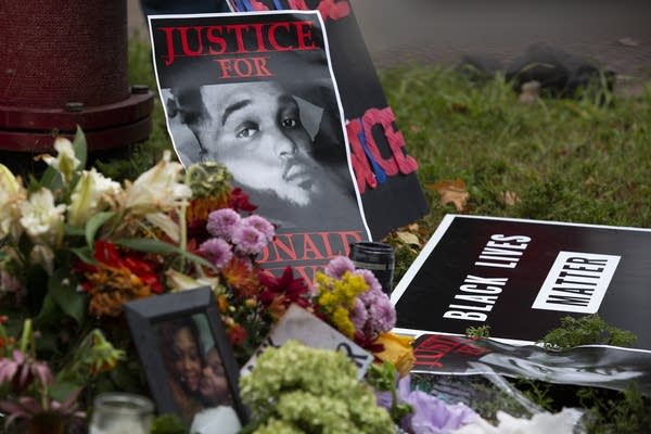 Posters, a framed photograph, and flowers are left on the ground