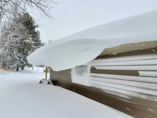 Massive snowdrifts hang from the eaves of a building