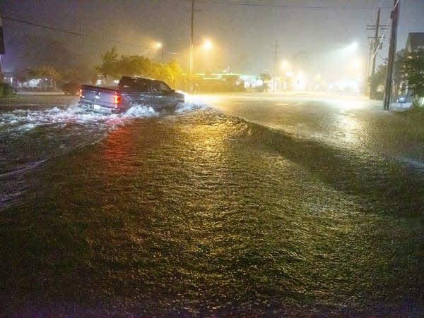 Motorists navigate a flooded boulevard