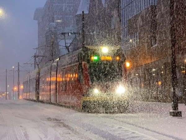 A Green Line train cuts through the snow in downtown St. Paul