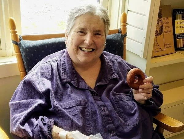 Joan Drury eating a donut at the World's Best Donuts in Grand Marais.