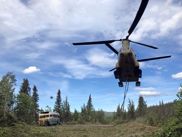 A CH-47 Chinook helicopter removes an abandoned bus