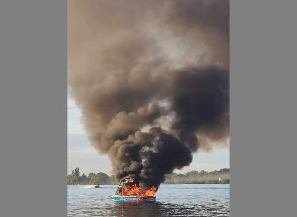 Photo of a boat completely on fire in a lake