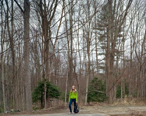 Carly stands in the woods near her home.
