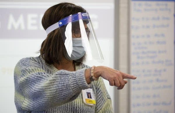 A teacher wearing a face shield and face mask.
