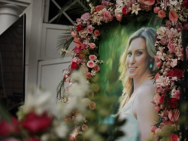 A photograph of Justine Ruszczyk surrounded with colored roses