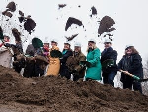 Local officials ceremoniously shovel dirt in the air.