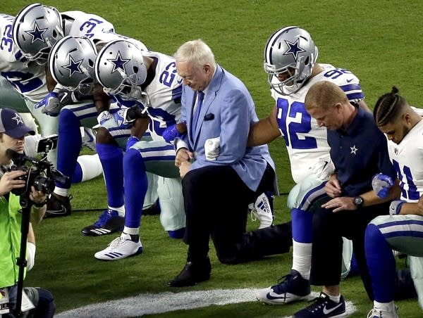 The Dallas Cowboys, led by owner Jerry Jones, center, take a knee