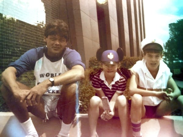 An adult and two children sit along the sidewalk.