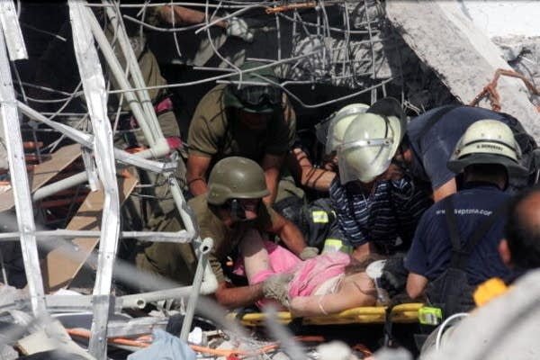 Rescue workers help an injured woman