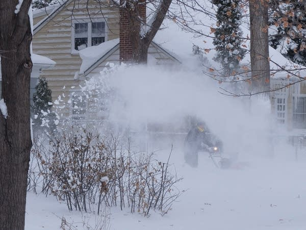 A snowblower blasts snow into the air.