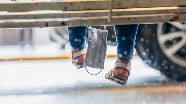 A few of two child-size feet and a face mask dangling from a bench
