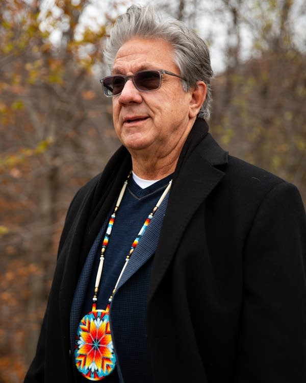 A man wearing a beaded necklace stands outside.
