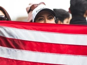 A woman peers from behind an American Flag.