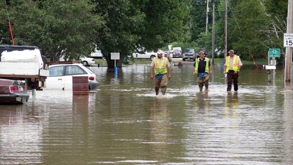 Workers walk down a flooded street in Freeport.