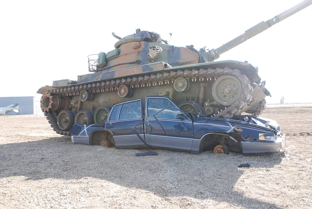 A tank crushes a car as part of a demonstration