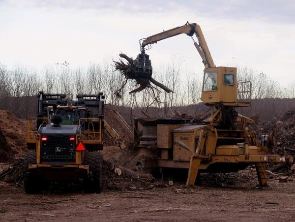 A worker scoops tree branches into a 1,000-horsepower tub grinder.