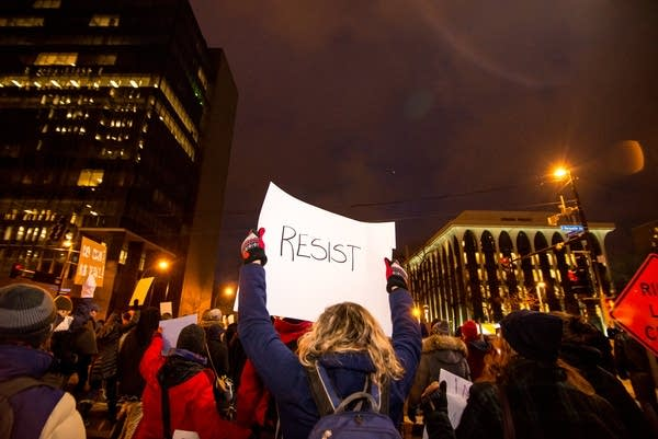 """A protester holds a sign that says """"Resist"""""""