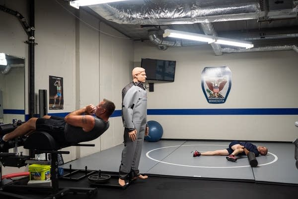 Police officers do sit-ups and stretch in a basement gym.
