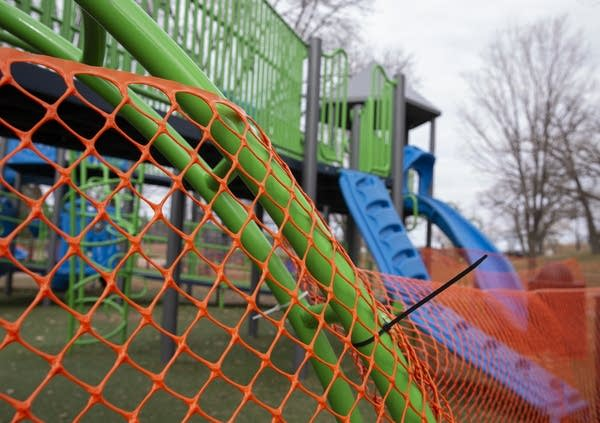 Orange fencing is wrapped around playground equipment.