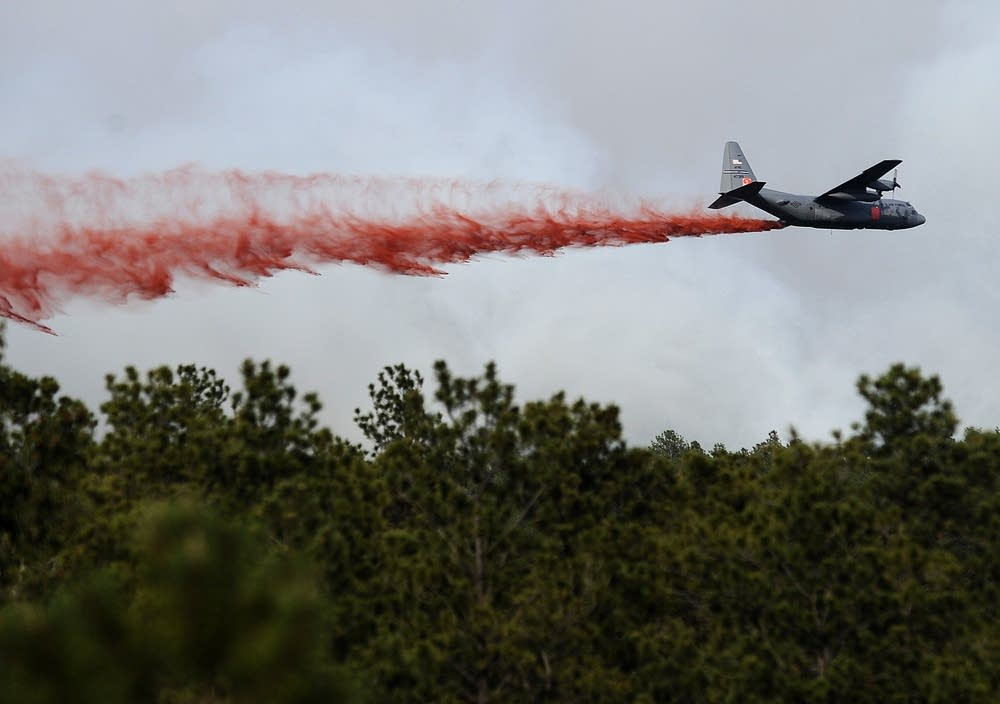 An airplane drops flame retardant