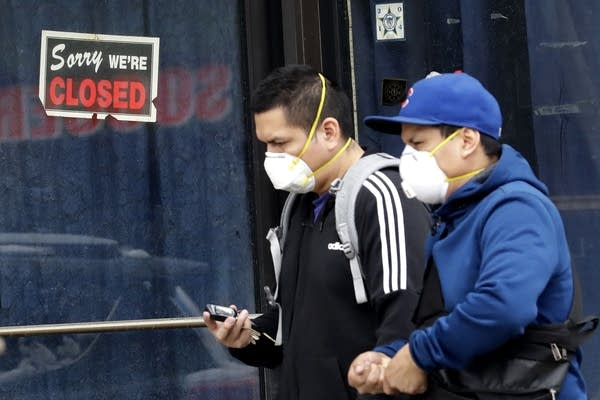Two people wearing masks walk past a closed sign at a retail store.