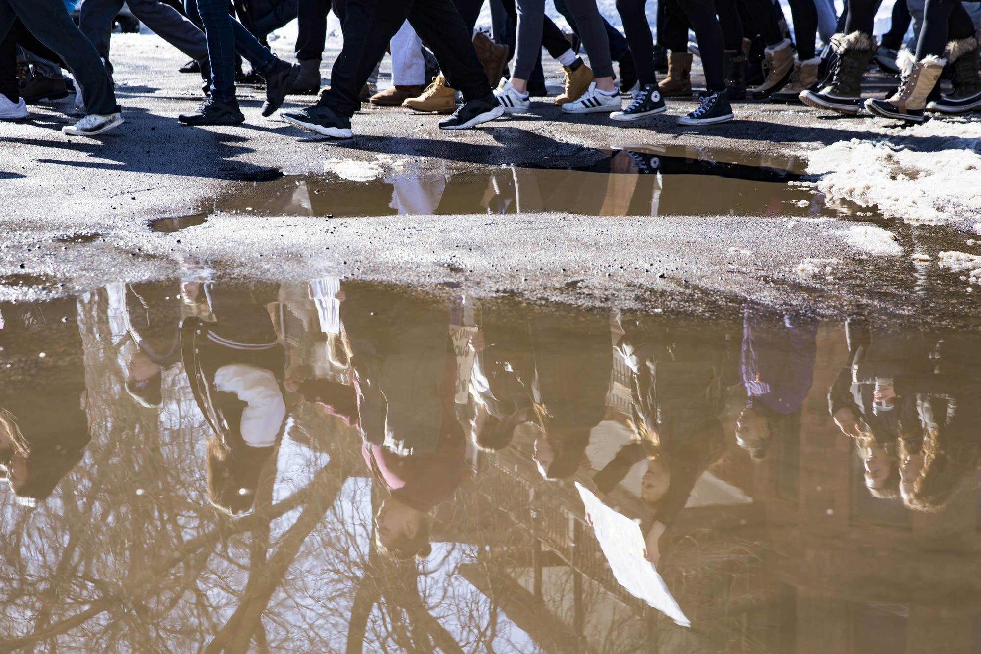 Marching students are reflected in a puddle