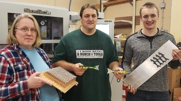 Three people pose for a photo holding metal objects.