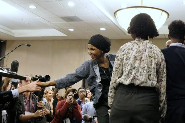 Ilhan Omar reaches out to a supporter after her victory speech.