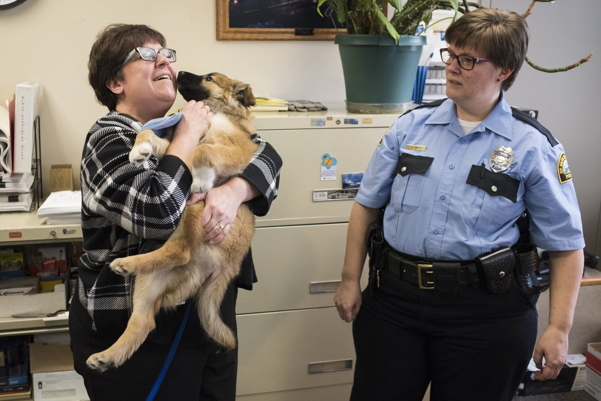 St. Paul Police Department employee Angela Anderson snuggles Sergeant Fuzz.