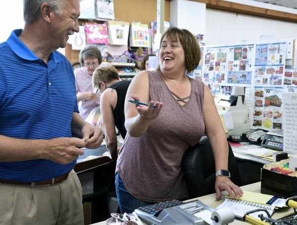 Bonnie Carlson visits with a customer in her store in Clinton, Minn.