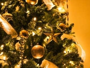 Ornaments decorate a Christmas tree.